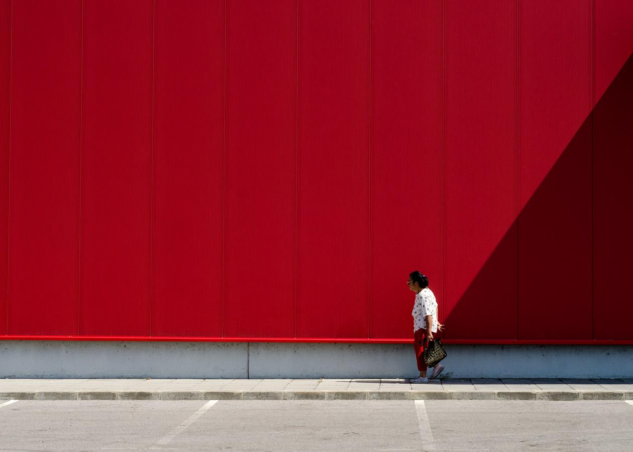 възрастната жена до една червена фасада