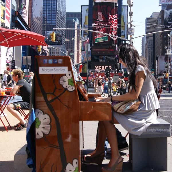 Жена свири на пиано на Times Square
